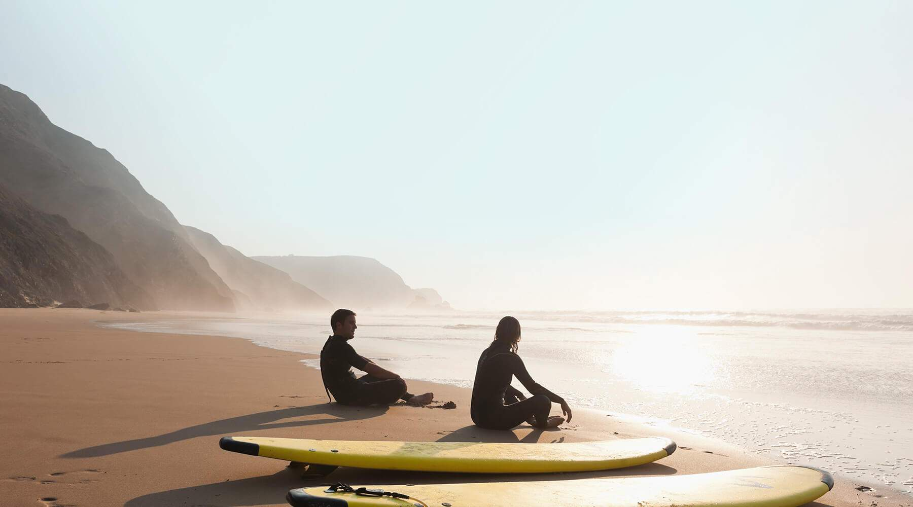 Couple sitting on beach with surf boards