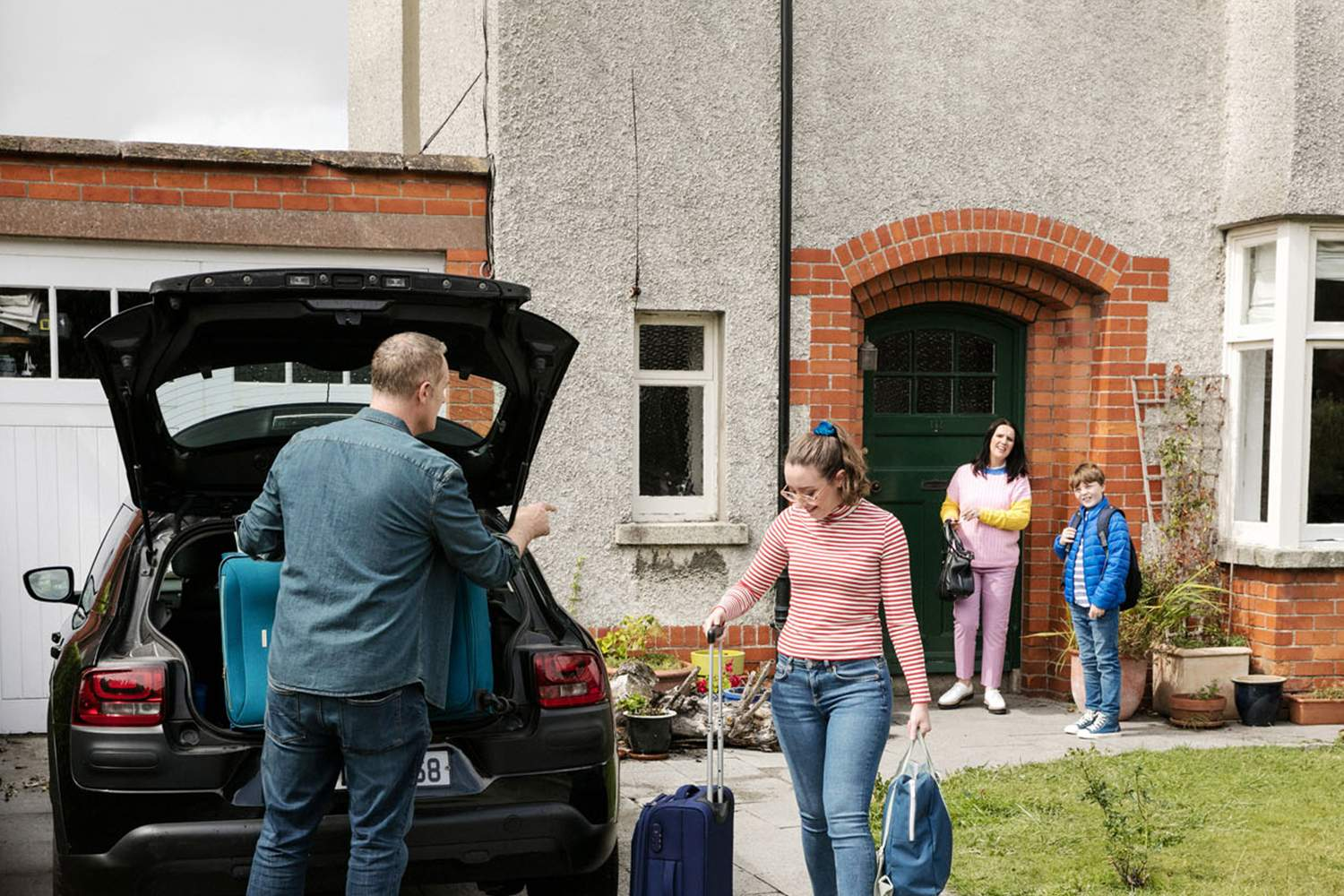 family packing suitcases into car